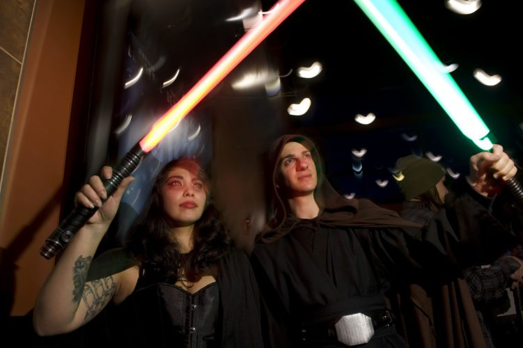 "Amanda Scott, 26, left, and Matt Manuel, 24, both of Stephens City, hold out their lightsabers inside the Alamo Drafthouse Cinema as they wait for the premiere of ""Star Wars: The Force Awakens"" on Thursday night. Rich Cooley/Daily"